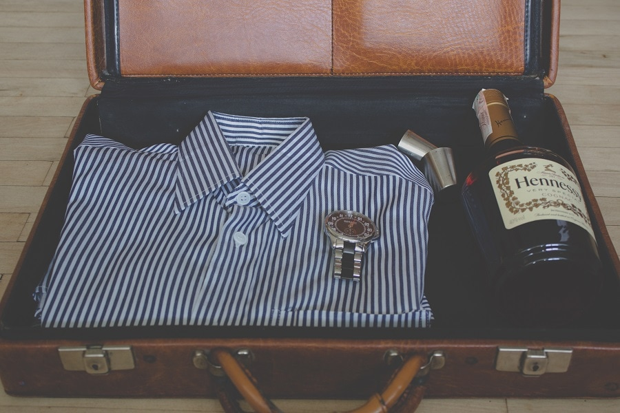 Suitcase with shirt and bottle of cognac